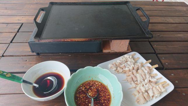 自宅の鉄板でホルモン串を焼いて、つけダレに付けて食べます。
